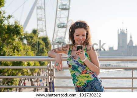 Woman looking at phone smiling, texting from bridge over River Thames, London with attractions in background - stock photo