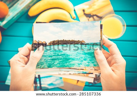 Woman looking at photos in her hands. Top view. - stock photo