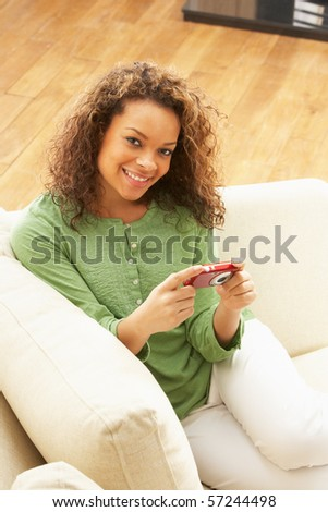 Woman Looking At Pictures On Digital Camera Relaxing Sitting On Sofa At Home - stock photo