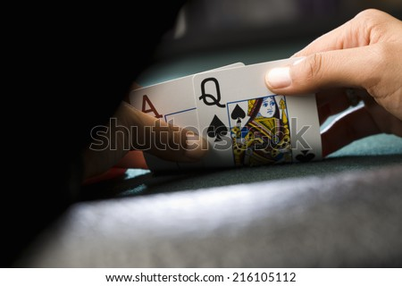 Woman looking at playing cards at poker table, close-up of hands - stock photo