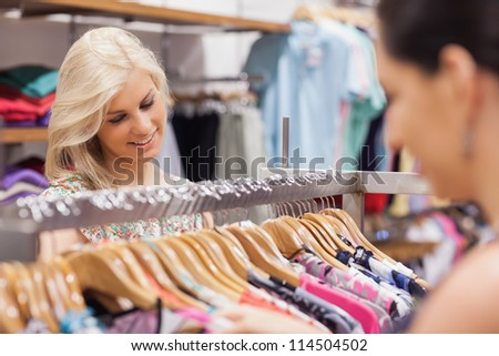 Woman looking at the clothes rack and smiling with friend - stock photo