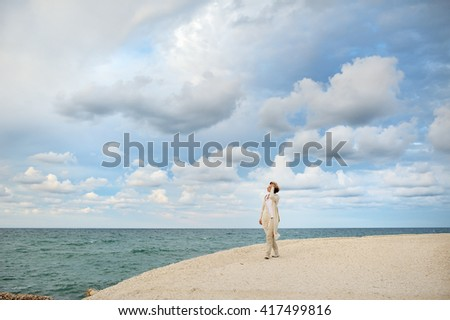 woman looking at the sea, on background cloudy sky - conceptual image, Ostuni, Apulia,mediterranean Italy