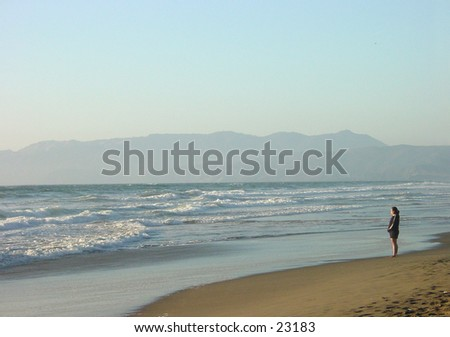 Woman looking at the sunset from Ocean Beach in San Francisco. - stock photo