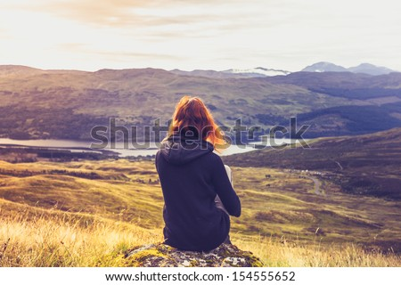 Woman looking at the sunset over mountains - stock photo