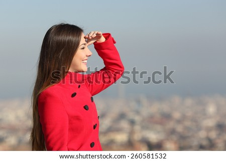 Woman looking forward in winter with a red coat with city in the background - stock photo