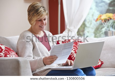 Woman looking happy while sitting at home doing home banking with laptop - stock photo