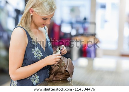 Woman looking in her bag in clothing store - stock photo