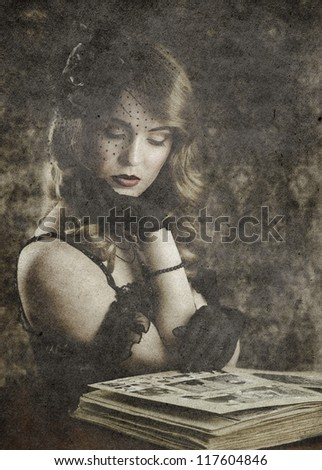 woman looking in old photo album, vintage portrait on retro background - stock photo