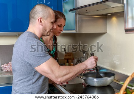 Woman looking into a pan her husband is holding in a kitchen - stock photo