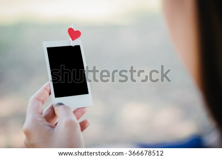 Woman looking love photo instant on hand and nostalgia lovers. 2 Blank instant photo and red clip paper heart. relationship concept. - stock photo