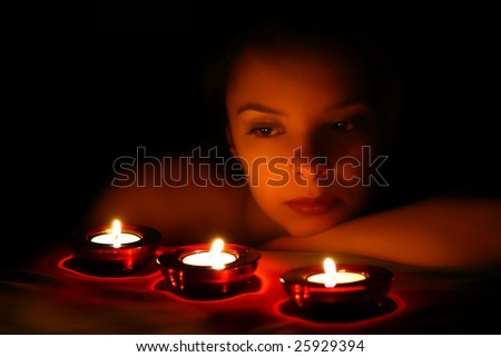Woman looking on three red candles - stock photo
