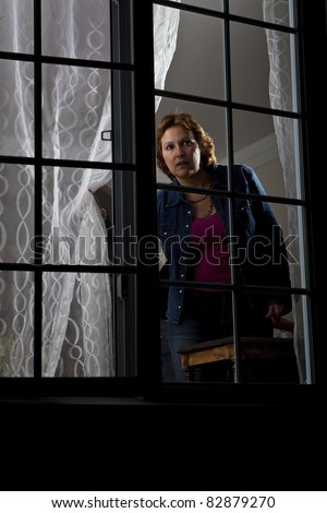 Woman looking out from behind a window - stock photo