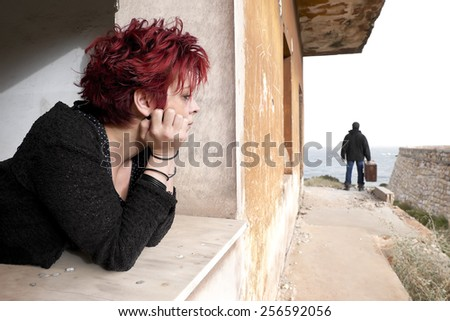 Woman looking out of the window at a man leaving her house - stock photo