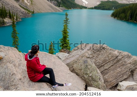 Woman looking out over beautiful Moraine lake in Banff National Park, Alberta, Canada  - stock photo