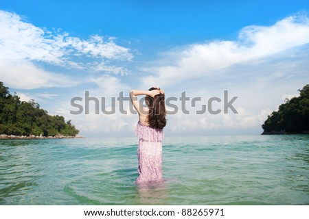 Woman Looking out to Sea in a very beautiful beach - stock photo
