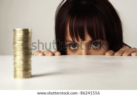 woman looking over her desk at a pile of english coins - stock photo