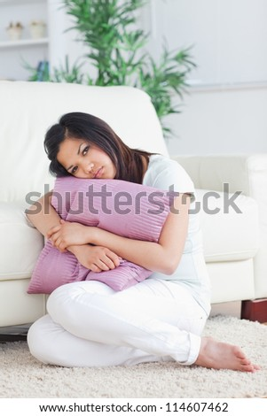 Woman looking sad while holding a pillow in a living room - stock photo