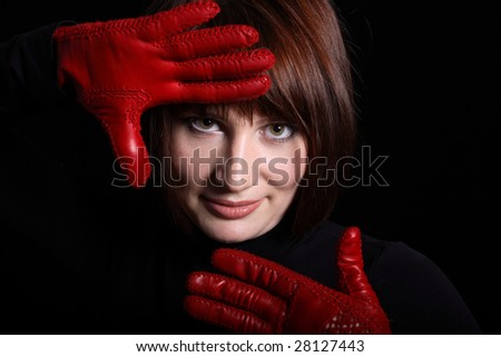 Woman looking straight from dark. In front of her red gloves on her hands. Horizontal - stock photo