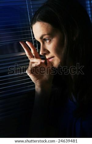 Woman looking though window. - stock photo