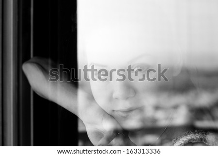 Woman looking through a window - stock photo
