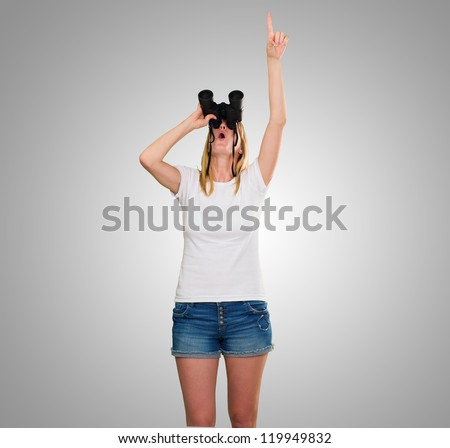 woman looking through binoculars and pointing up against a grey background - stock photo