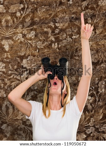 woman looking through binoculars and pointing up against a vintage background - stock photo