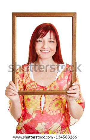 Woman looking through empty wooden picture frame