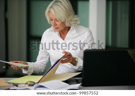 Woman looking through some files - stock photo