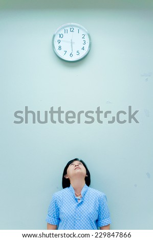 woman looking up clock - stock photo