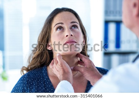 Woman looking up while getting examined by doctor in clinic - stock photo