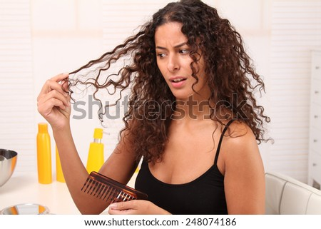 woman looks at her broken hair - stock photo