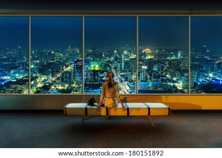 Woman looks at night cityscape - stock photo