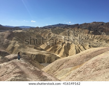 Woman looks out at Zabriskie Point, Death Valley, California