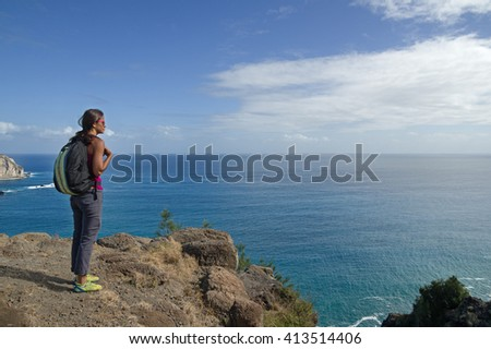 woman looks out over the Pacific Ocean from Makapuu Point on Oahu Hawaii - stock photo
