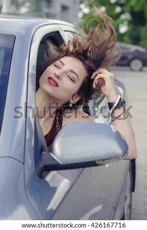 Woman looks out the car window and her hair fluttering in the wind. Concept: business, lifestyle, freedom - stock photo