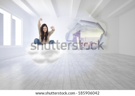 Woman looks straight ahead as she celebrates in front of her laptop against rip on wall showing cityscape - stock photo