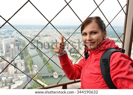 woman looks through telescope on top of the Eiffel