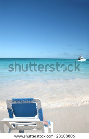 Woman lounging in a chair on a beautiful Caribbean tropical beach with white sand and green ocean, suitable background for a variety of designs - stock photo