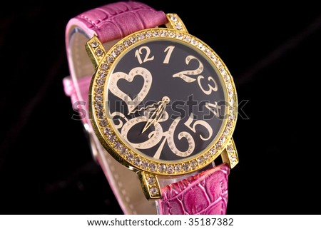 Woman luxury watch in golden tone with crystals and ping strap. - stock photo