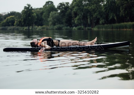 woman lying and relaxing on a paddle board on a lake surrounded by trees