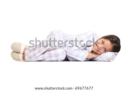 Woman lying down cute in pajamas and slippers. Isolated on white background. Mixed race Asian Chinese / white Caucasian girl. - stock photo