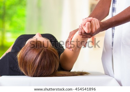 Woman lying down getting physical arm treatment from physio therapist, hands working on her elbow area, medical concept - stock photo