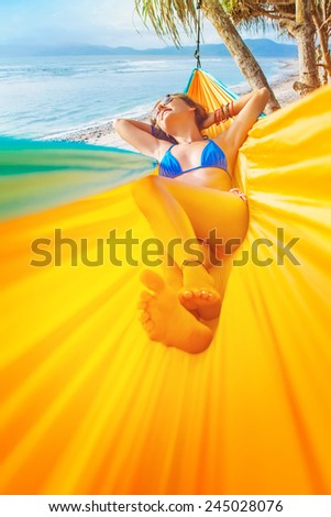 woman lying down in a colorful hammock - stock photo