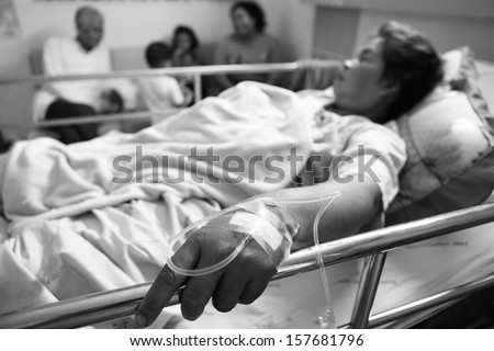 Woman Lying Down In Hospital Bed in black and white - stock photo