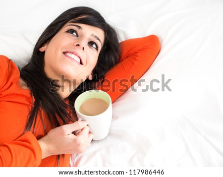 Woman lying down on bed with cup of coffee in the morning. Happy breakfast and day dreaming. Copy space. - stock photo