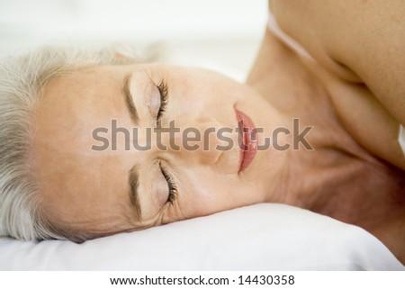 Woman lying in bed sleeping - stock photo