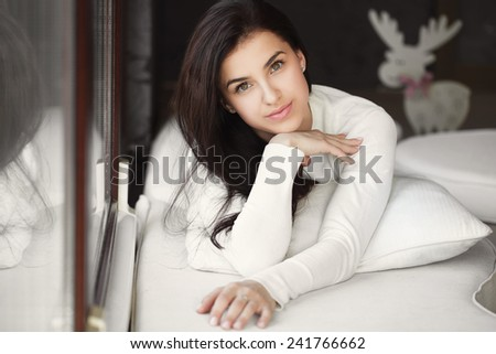 Woman lying in bed smiling. lady laying in bedroom at early morning. Woman lying in bedroom smiling near window. - stock photo