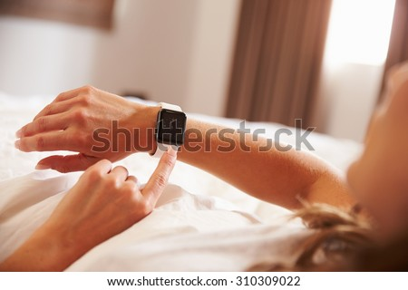 Woman Lying in Bed Whislt Checking The Time on Smart Watch - stock photo