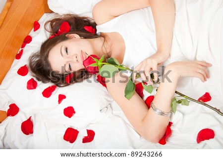 Woman lying in bed with a rose