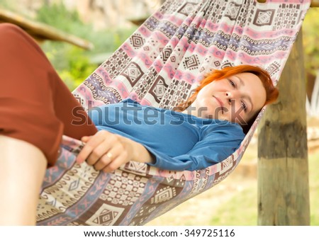 Woman lying in Hammock at Patio of Wooden Rural Cottage relaxed and serene smiling positive green Garden on background - stock photo